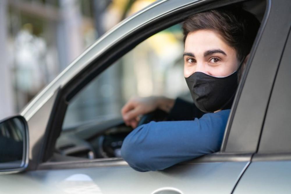 Motorista em um carro com máscara