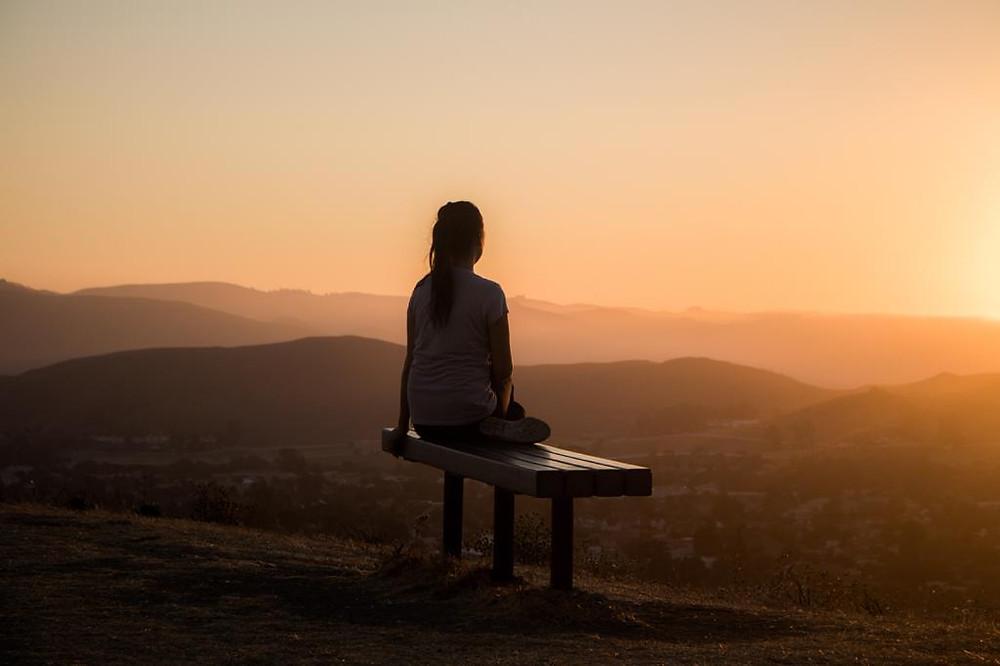 Mulher sentada em um banco admirando a paisagem