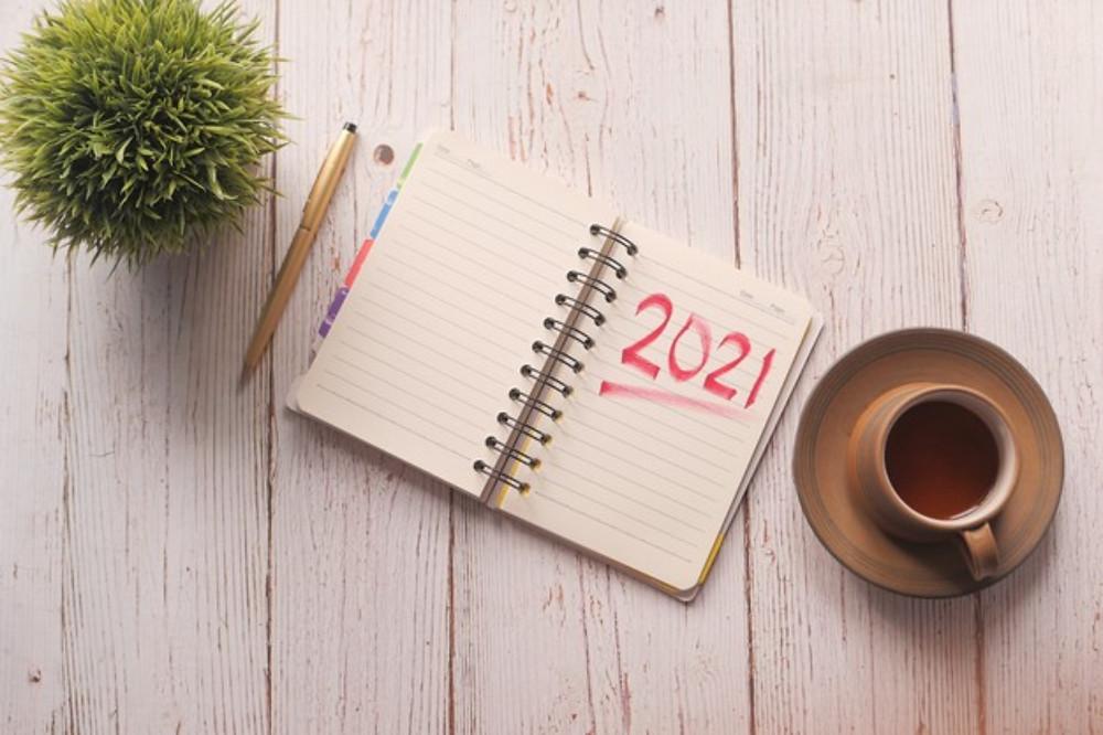 Agenda com o número 2021 escrito ao lado de uma caneta, um vaso decorativo e uma xícara de café