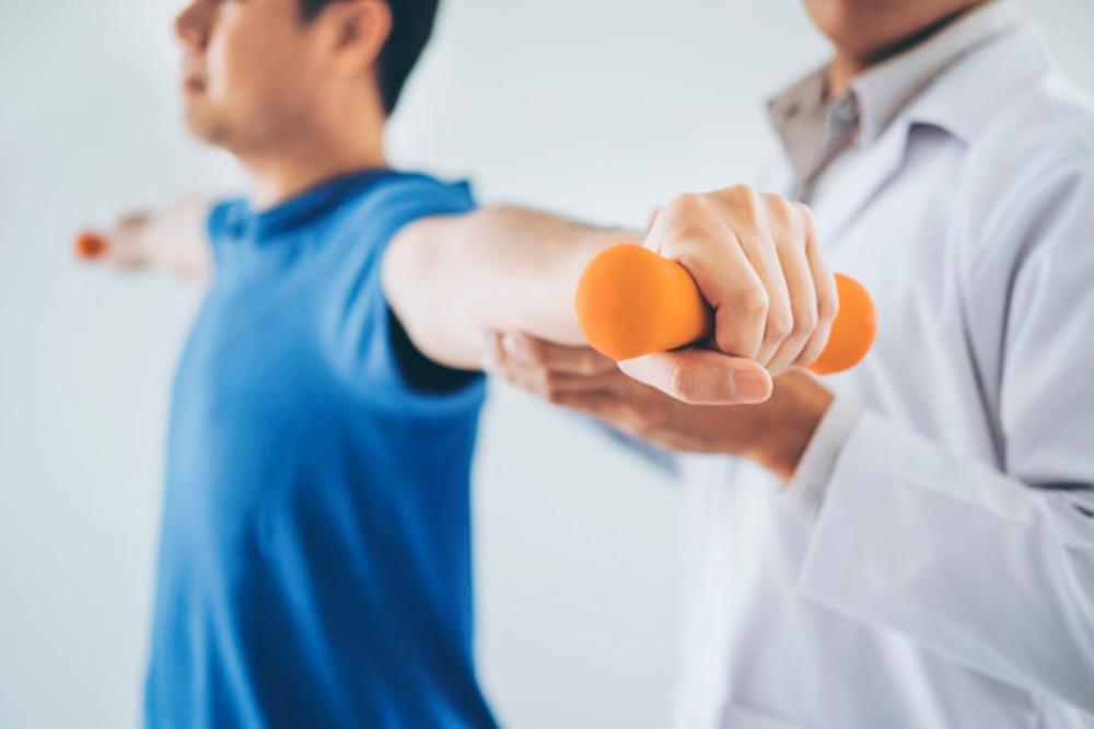 Médico ajudando paciente homem a realizar exercício