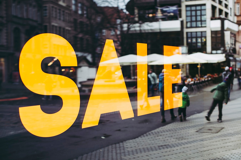 """Loja adesivo escrito """"Sale"""" no vidro"""