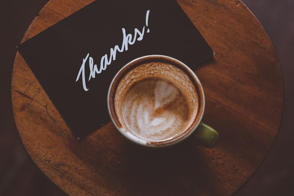 """Xícara de café com um bilhete ao lado escrito """"Thanks"""""""