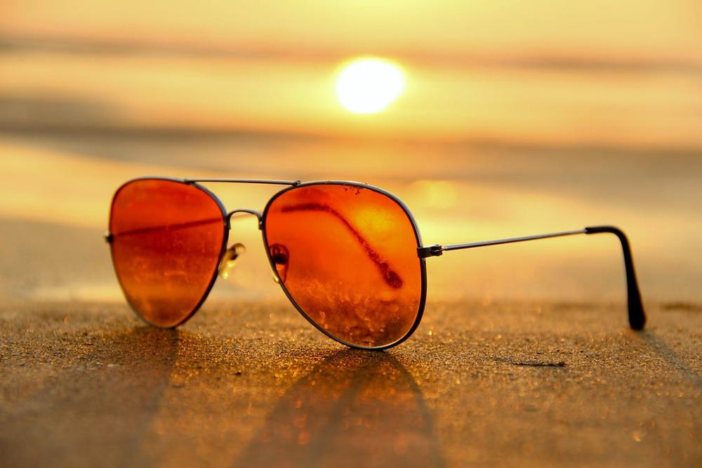 Óculos de sol lente laranja no chão