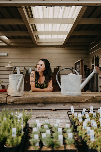 A woman with long, black hair,smiles, standing next to watering cans in a garden shed.