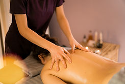 A massage therapist gives a woman a back massage.