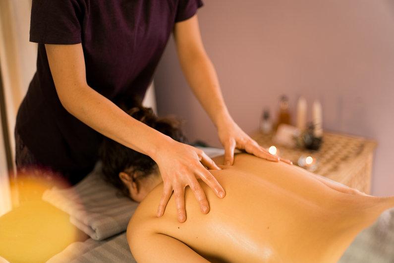a massage therapist gives a woman a back massage