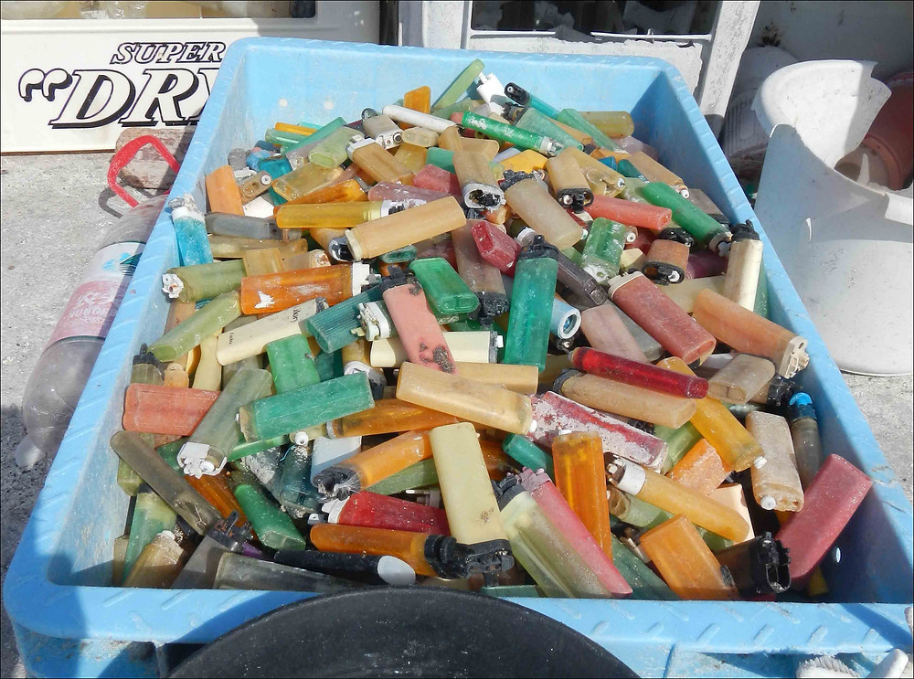 The contents of the plastic crate in this photo make up just a portion of the 1249 cigarette lighters found on the shorelines of Midway Atoll during this mission. NOAA photo by Kristen Kelly
