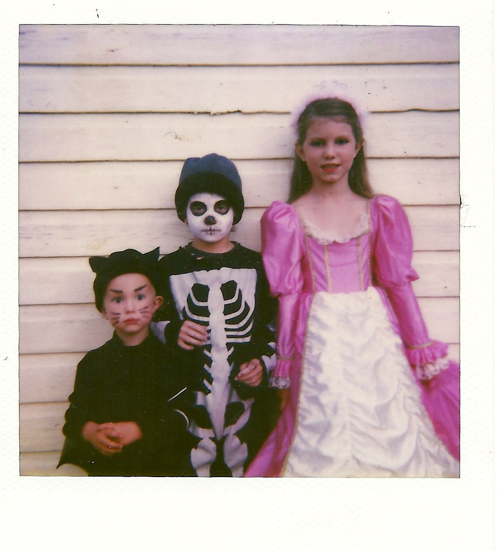 three young children in Halloween costumes