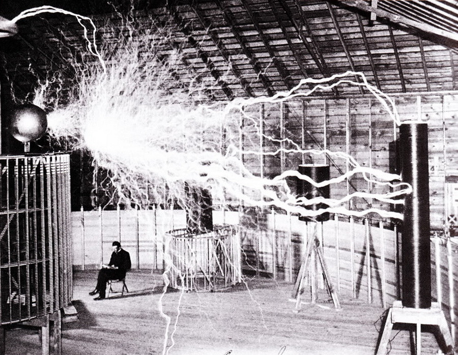 Electrical currents streaking across a room, man sitting underneath