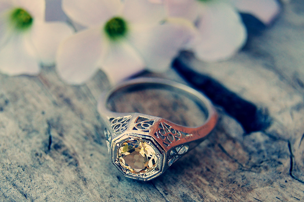 vintage ring, yellow diamond, white gold ring, silver ring, silver engagement ring, white gold engagement ring, die-struck ring, flowers, ring on shelf, ring on bench, antique ring,