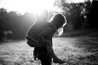 Sort og hvid billede af to søskende, der leger hest og rytter