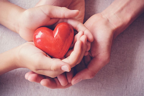 adult and child hands holding red heart,