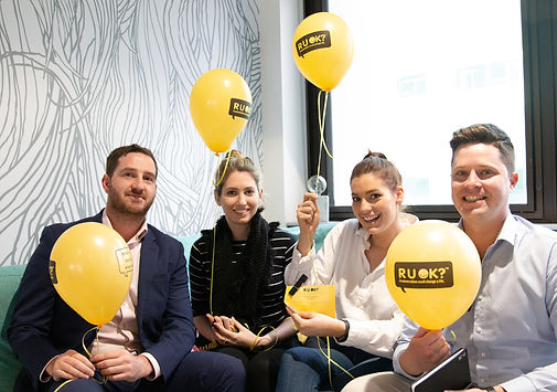 """Brisbane business employees posing for a photo with yellow balloons reading """"r u ok?"""""""