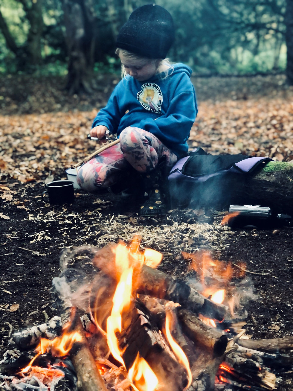 image of a child in the woods neara fire, whittling a stick.