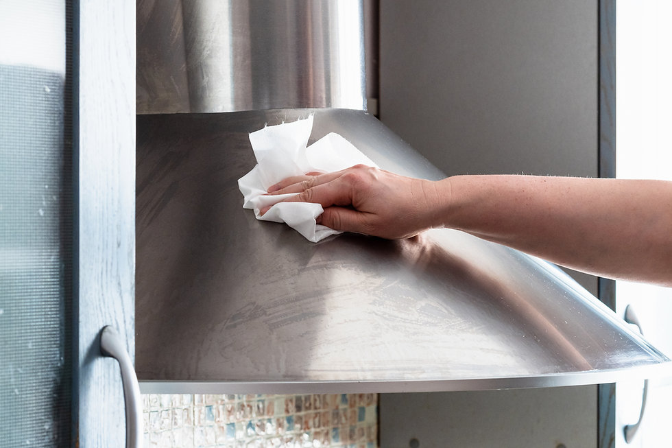 female hand wipes stainless steel range hood at home kitchen.jpg