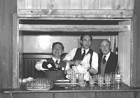 Three Freemasons serving behind the bar
