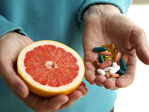 Man holding grapefruit in one hand and various pills in the other