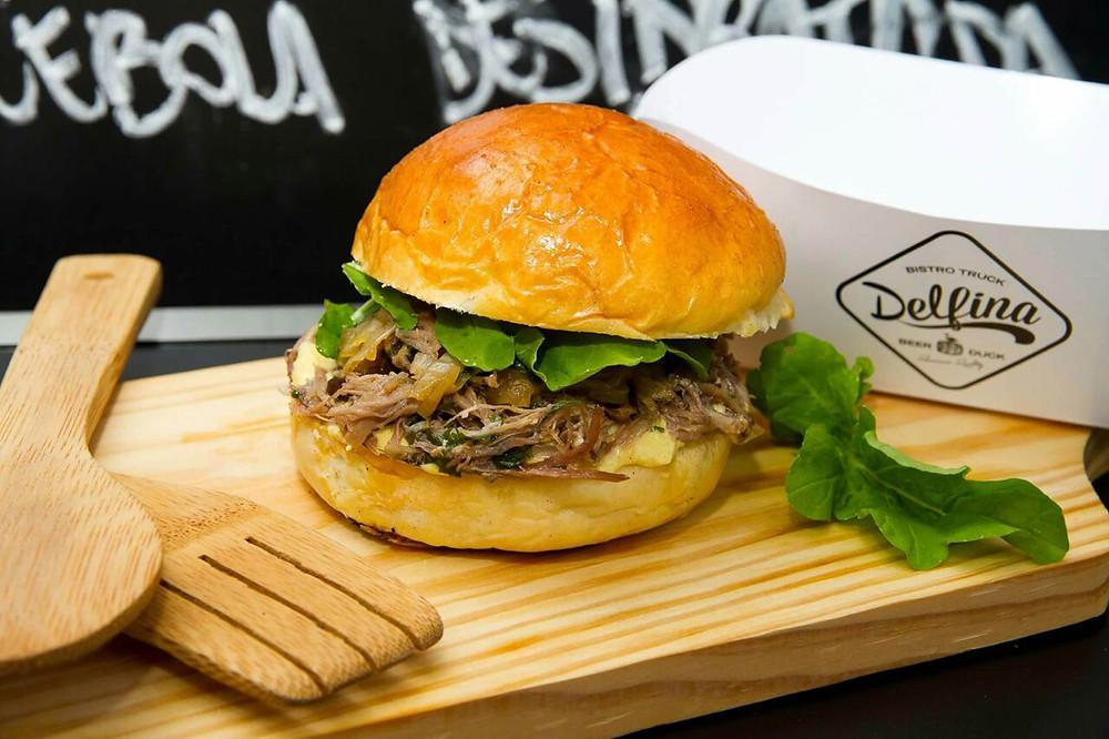 sanduíche de pato servido no pão brioche, com mostarda Dijon, Aïoli, cebola caramelizada e rúcula