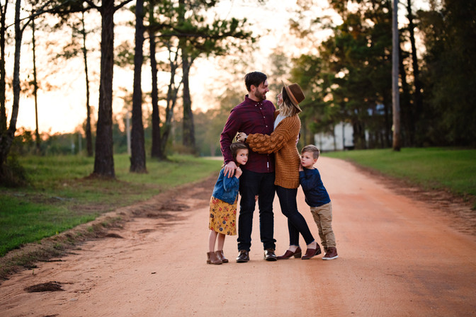 family of four outdoor photoshoot standing on dirt road