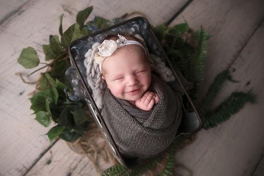 Swaddled newborn smiling