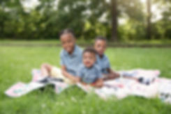 Three brothers sitting on quilt outside smiling