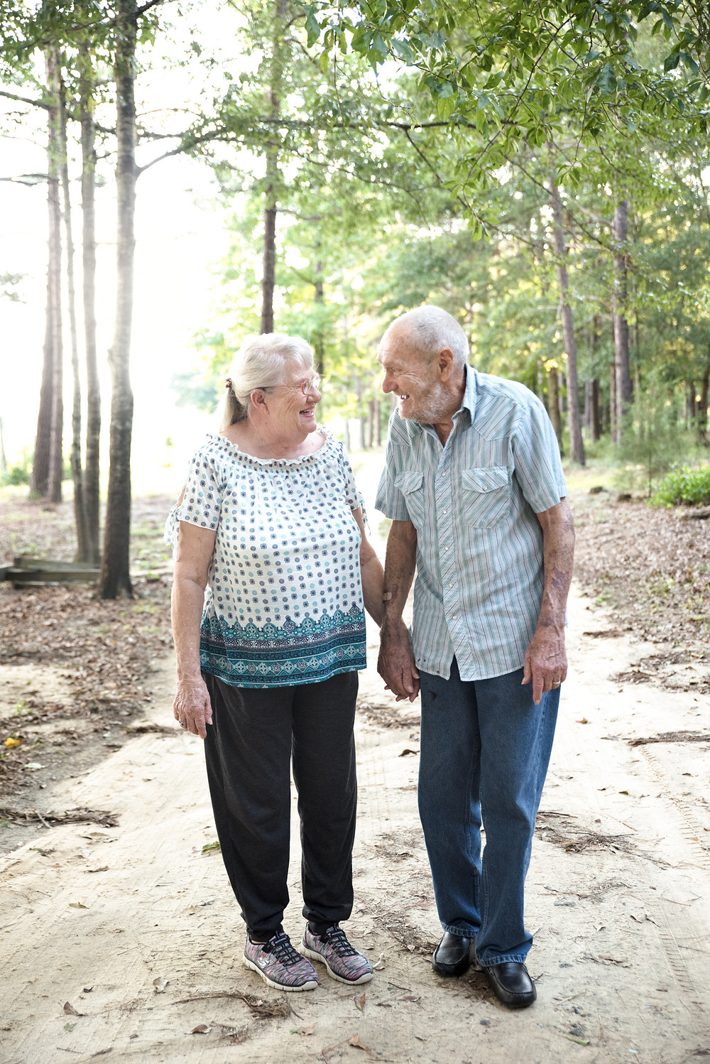 Elderly couple smiling at each other while holding hands