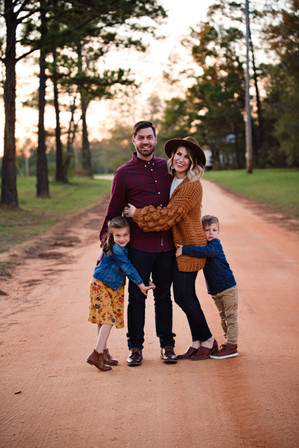 smiling family of four photoshoot standing on dirt road