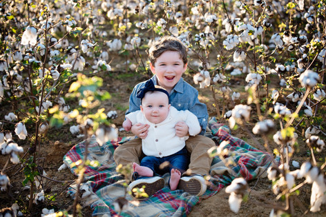 brother and sister smiling in cotton field