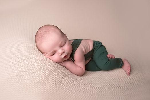 sleeping newborn boy wearing suspenders posed studio session