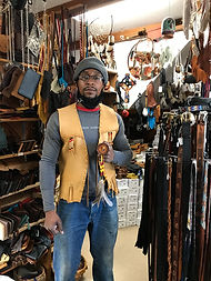 Man in handmade leather vest in Four Winds Leather Shop among leather and native american items