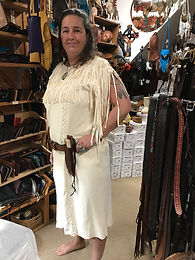Woman wearing light-colored handmade deerskin dress with leather knife holster at Four Winds Leather Shop