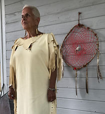 Woman with handmade deerskin dress beside handmade dreamcatcher
