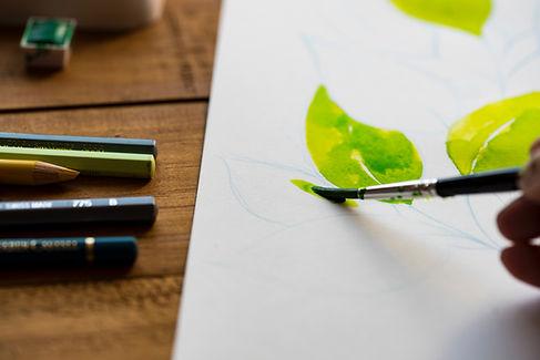 Aluna pintando na Desenhe utilizando pincel e tinta aquarela.
