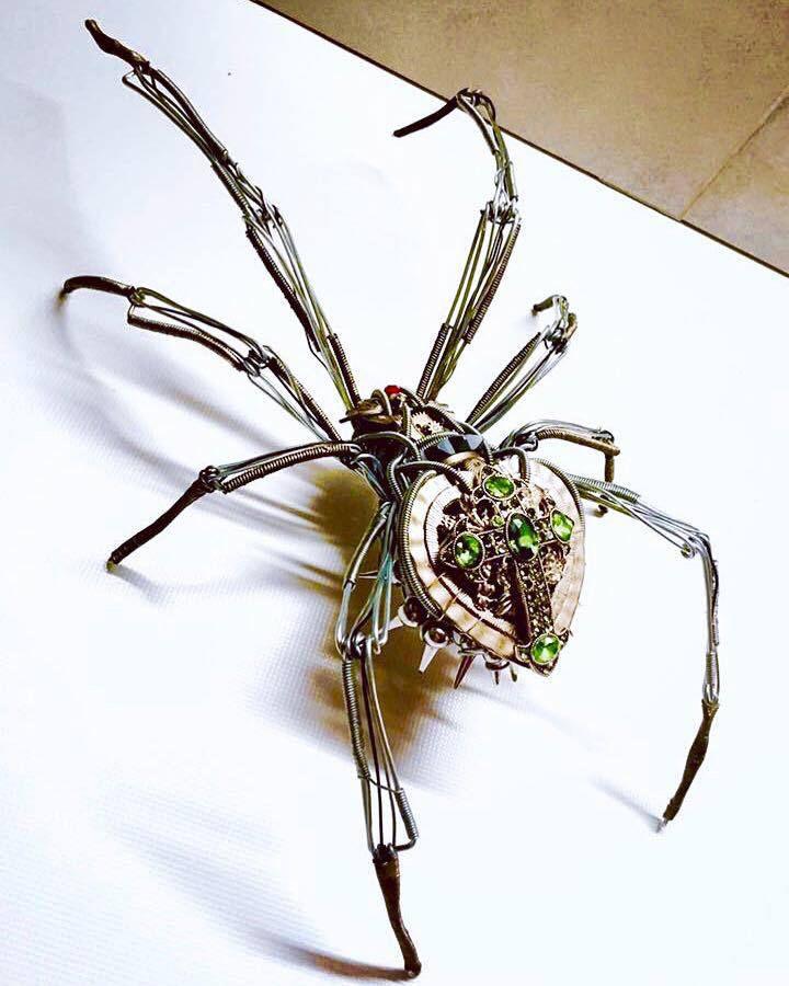 Sculpture d'une araignée de métal réalisée à partir de fil de fer, pièces de montre et autres mécanismes