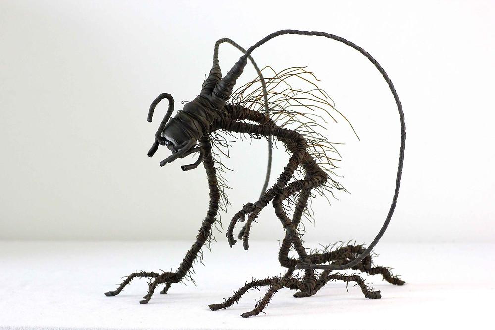 Créature démoniaque réalisée via l'assemblage de fils de fer, embout de tuyau d'arrosage et chambre à air de vélo