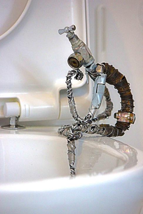 Robot robinet en métal de récupération, pensant au bord des toilettes