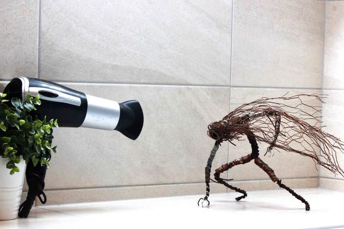 robot en recyclage face à un séchoir à cheveux