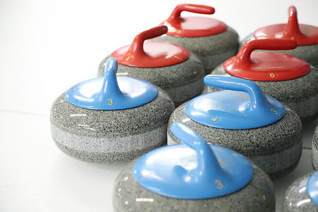 Set of the Rideau's curling rocks. Image shows three blue and four red rocks.