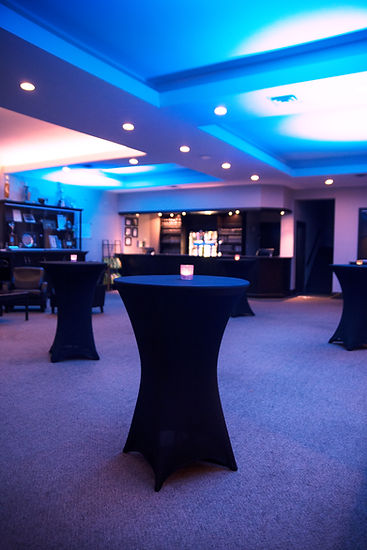The downstairs lounge set up with cocktail tables, candles and blue uplighting to show event setups.