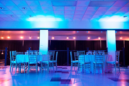 Upstairs banquet hall with two tables dressed for a wedding. Hall is backlit in purple.