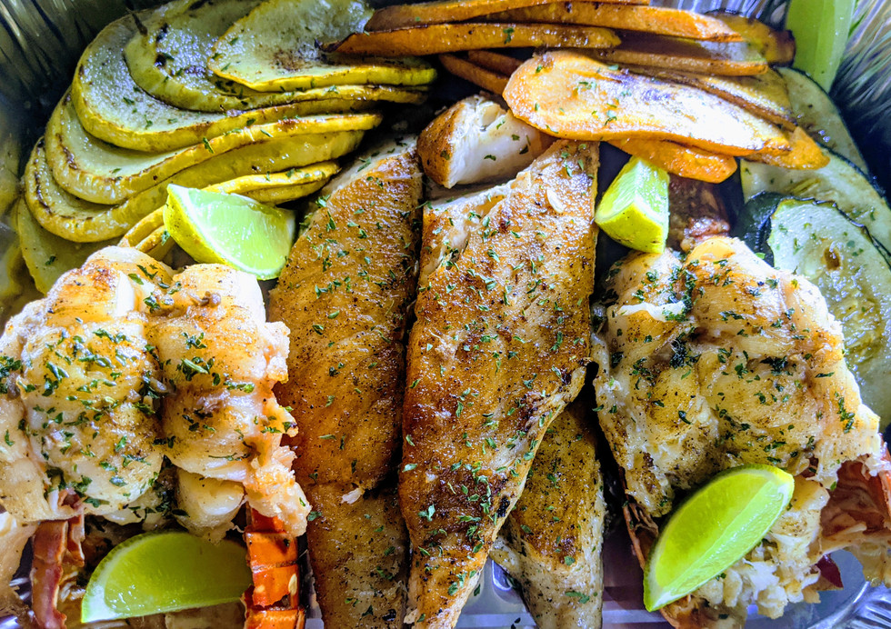 Custum family order of twining lobsters and grilled fillet fish served with grilled vegetables.