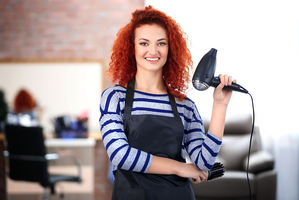 Red-haired lady holding a hair dryer in a new hair salon