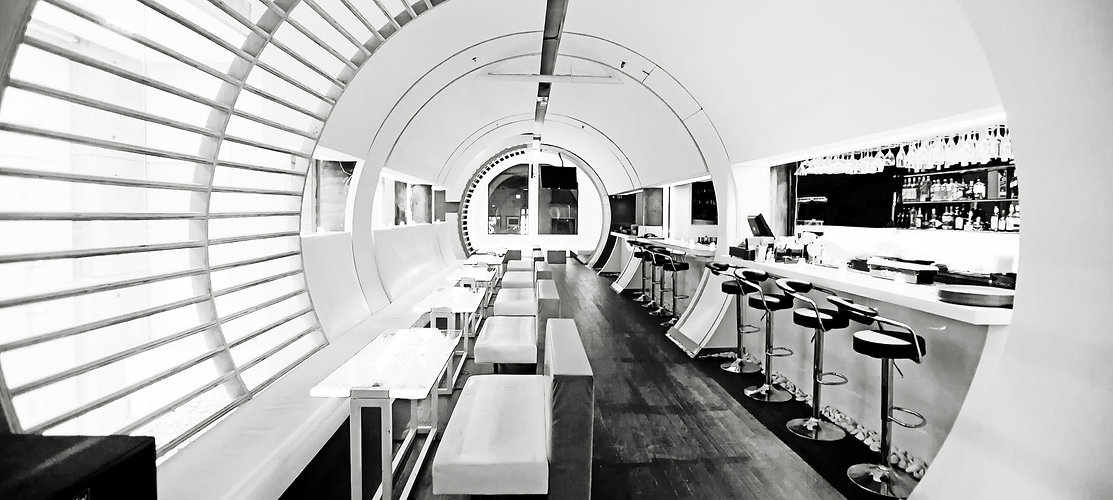 Maru 4th floor interior - Round tunnel and spaceship alike interior with tables, seating, bar and bar stools in black & white photo.