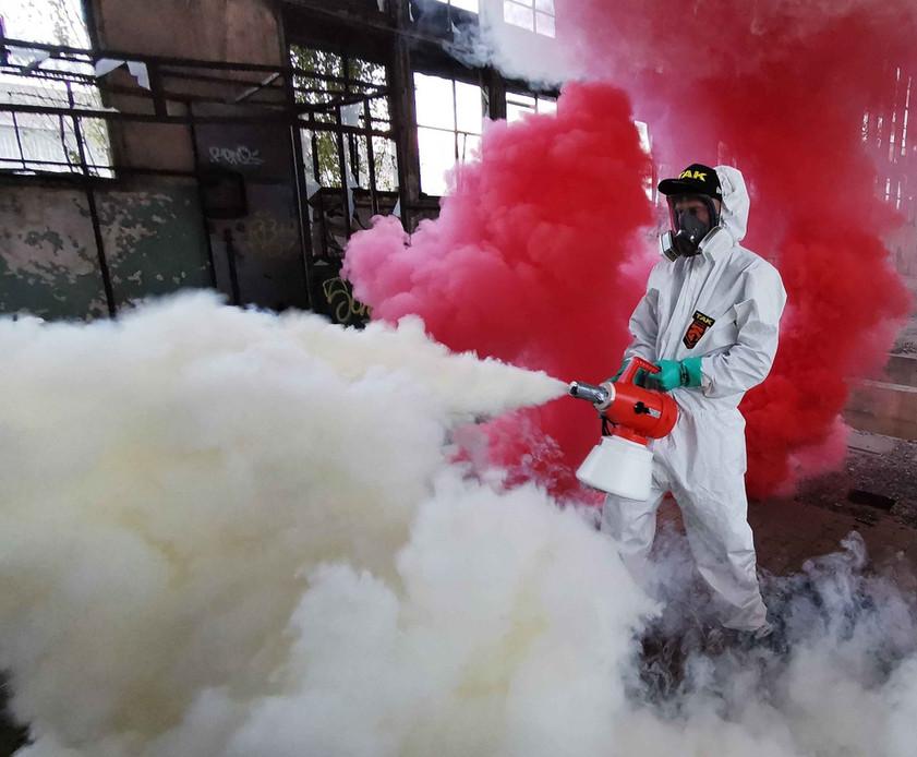 A Takarító Kommandó munkatásra, a takarító személyzet egy tagja hidegködös fertőtlenítést végez védőruhában és maszkban   Fertőtlenítő takarítás