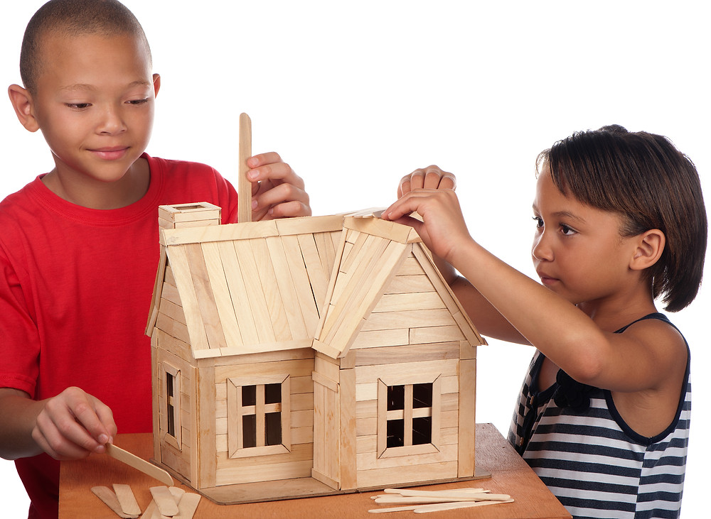 children building a house out of sticks