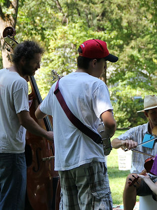 banjo, bass, guitar, and fiddle players at summer camp jam playing together