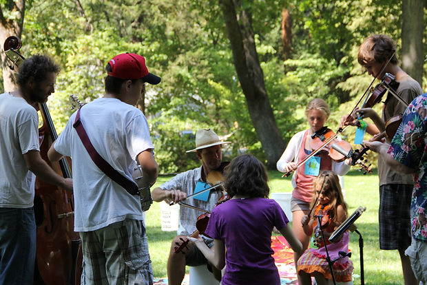bass, banjo, and fiddle players jamming at a summer camp