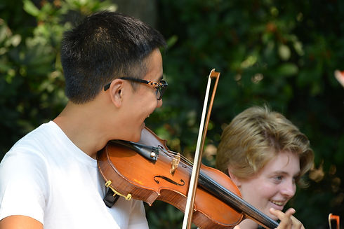 A happy fiddle student playing at a camp