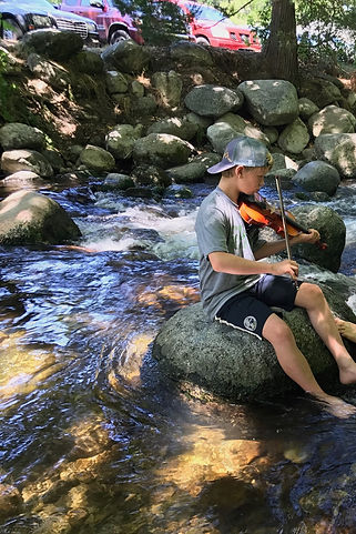 fiddle student learning by ear at summer camp in beautiful creek