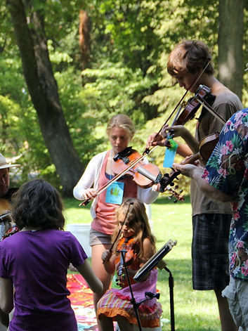 Fiddle and violin students, teachers, and parents playing outside at a community jam